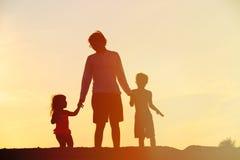 生与走在日落的儿子和女儿 免版税库存图片