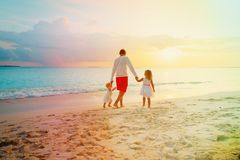 生与走在海滩的两个孩子在日落 库存图片