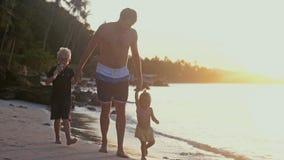 生与走在海滩的孩子在美好的日落 旅行假日概念 库存图片