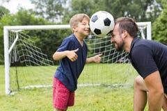 生与踢在橄榄球球场的儿子橄榄球 免版税图库摄影