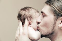 生与他的拥抱和亲吻他的年轻婴孩在面颊 免版税库存照片