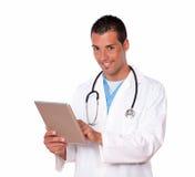 年轻医生与他的片剂个人计算机一起使用 免版税库存图片