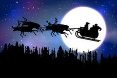 生乘坐他的与驯鹿的圣诞节雪橇在满月前面的一个森林在蓝色满天星斗的天空背景 库存图片