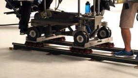 生产人员设置移动式摄影车轨道在演播室 免版税库存照片