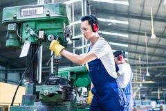 生产工厂钻井的亚裔工作者 免版税图库摄影