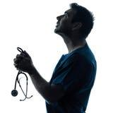 医生人祈祷的剪影画象 免版税库存图片
