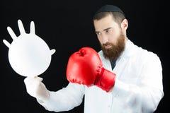 医生佩带的拳击手套藏品膨胀的手套 免版税图库摄影