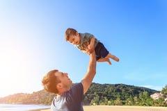 生使用与他的海滩的儿子在日落时间 免版税图库摄影