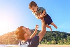 生使用与他的海滩的儿子在日落时间 免版税库存图片