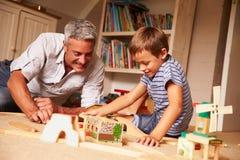 生使用与儿子和玩具在地板上在游戏室 库存照片