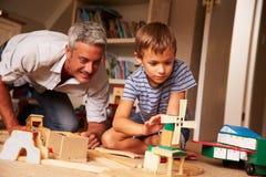 生使用与儿子和玩具在地板上在游戏室 免版税图库摄影
