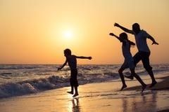 生使用在海滩的儿子和女儿在日落时间 图库摄影