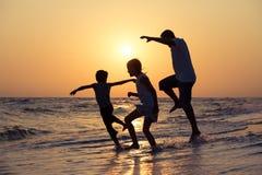 生使用在海滩的儿子和女儿在日落时间 免版税库存照片