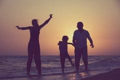 生使用在海滩的母亲和儿子在日落时间 免版税库存图片