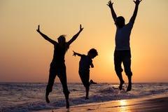 生使用在海滩的母亲和儿子在日落时间 图库摄影