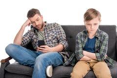 生使用智能手机并且让小儿子烦恼坐有横渡的胳膊的沙发 免版税库存图片