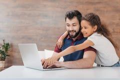 生使用膝上型计算机,当拥抱他和指向屏幕时的愉快的女儿 免版税库存图片