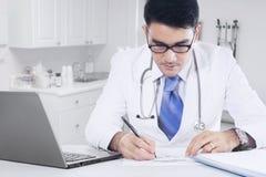 医生做在诊所的医学食谱 免版税图库摄影