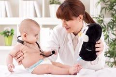 医生儿科医生和耐心愉快的儿童婴孩 免版税库存照片