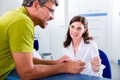 医生办公室的招待会的患者 免版税库存照片