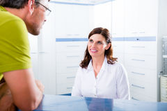 医生办公室的招待会的患者 免版税图库摄影