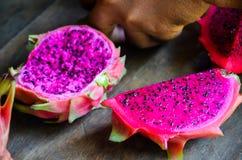 生动和充满活力的红色龙果子在老木桌, Phat的池氏,柬埔寨上切开了 库存照片