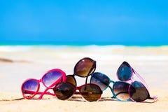 生动描述许多太阳镜说谎在热带海滩 免版税库存照片