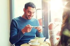 生动描述食物的愉快的夫妇由智能手机在咖啡馆 库存图片