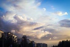 生动的多云天空背景在城市 库存图片