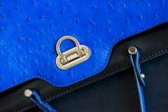 生动的时尚蓝色颜色提包,与装饰的真皮特写镜头纹理在驼鸟下,金锁皮肤  库存照片