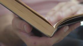 生叶通过书户内特写镜头的页的男性手 知识,教育,休闲的概念在家 股票录像