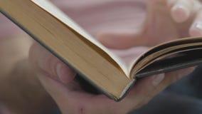 生叶通过书的页的男性手特写镜头户内 知识,教育,休闲的概念在家 影视素材