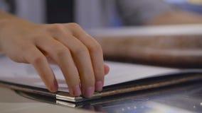 生叶通过在餐馆或咖啡馆菜单的页的妇女的特写镜头 股票视频