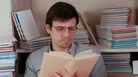 生叶通过坐在书中的书的页的玻璃的年轻深色的人 股票视频