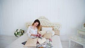 生叶通过杂志和读的新闻页的主妇,坐大床 库存照片