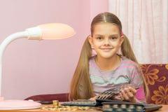 生叶通过硬币收藏家的一个册页的孩子和调查框架 免版税图库摄影