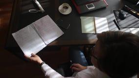 生叶通过笔记本的妇女在桌上 股票视频