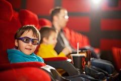 生和两个孩子,男孩,观看在cin的动画片电影 免版税库存照片