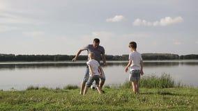 生和两踢在海滩的儿子橄榄球在天时间 友好的家庭的概念 股票录像