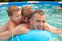 生和他的子项获得乐趣在池 免版税图库摄影