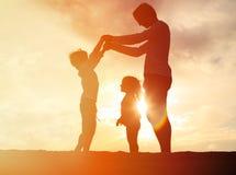 生和使用在日落天空的两个孩子 库存照片