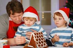 生和准备姜饼曲奇饼房子的两个小儿子 免版税图库摄影
