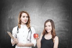 医生和妇女用苹果 库存图片