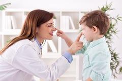 医生和孩子享用和演奏一起接触鼻子 免版税库存照片