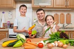 生和家庭厨房内部的两个孩子 愉快的家庭、获得女孩和的男孩乐趣用水果和蔬菜 健康食物C 图库摄影