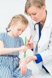 医生和小女孩使用毡尖的图画绷带 免版税库存照片