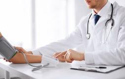 医生和患者测量的血压 免版税库存照片