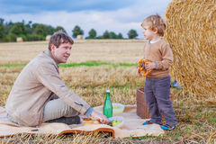 生和有他的小逗人喜爱的孩子的儿子在麦田的野餐 图库摄影
