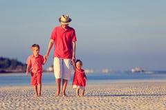 生和走在夏天海滩的两个孩子 库存照片