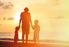 生和走在日落海滩的两个孩子 库存图片